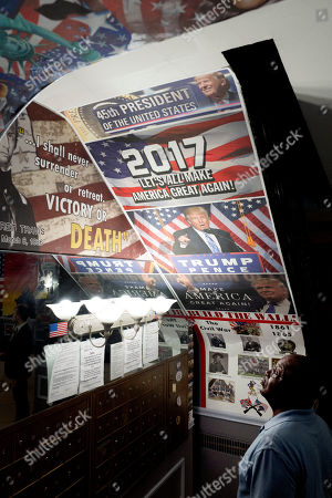 A man looks at a series of posters in the lobby of an apartment building, in the Queens borough of New York. In addition to posters of President Donald Trump, the lobby has racist and anti-semitic images. According to New York City Councilman Jimmy Van Bramer, the building's property manager has posted the images to harass the residents