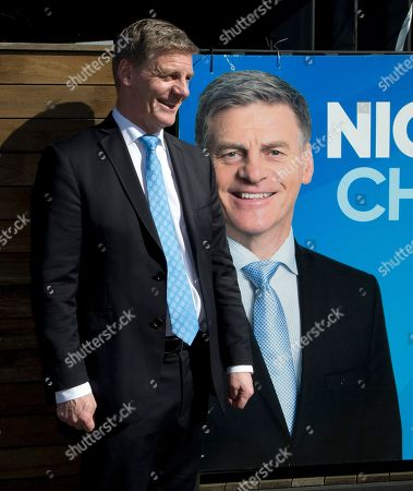 New Zealand Prime Minister Bill English stands by a billboard with his photo displayed on it in Christchurch, New Zealand, . New Zealand will hold a general election on Saturday, Sept. 23, 2017