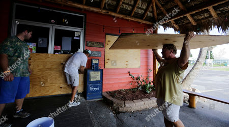 Mac Owens, Mark Jones, Kelly Owens Mac Owens, left, Mark Jones, center, and Kelly Owens, right, board up their business in preparation for Hurricane Harvey, in Port Aransas, Texas. Harvey intensified into a hurricane Thursday and steered for the Texas coast