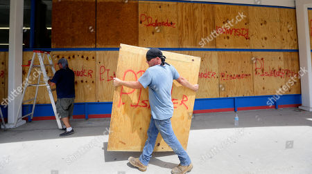 James Redford carries a sheet of plywood as he helps board up windows in preparation for Hurricane Harvey, in Corpus Christi, Texas
