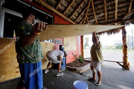 Mac Owens, Mark Jones, Kelly Owens Mac Owens, left, Mark Jones, center, and Kelly Owens, right, board up their business in preparation for Hurricane Harvey, in Port Aransas, Texas