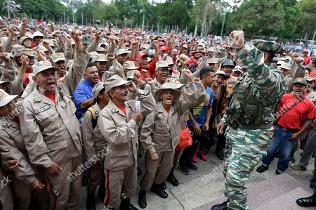 Militia members cheer the commander of the Venezuelan Bolivarian Militia, Gen. Carlos Leal Telleria, in Fort Tiuna, Caracas, Venezuela, . President Nicolas Maduro ordered military exercises in response to President Donald Trump's warning of possible military action to resolve the country's crisis