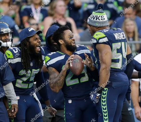Seattle Seahawks cornerback Richard Sherman, free safety Earl Thomas, center, and middle linebacker Bobby Wagner (54) react on the sideline during the second half of an NFL football preseason game against the Kansas City Chiefs, in Seattle. The Seahawks won 26-13