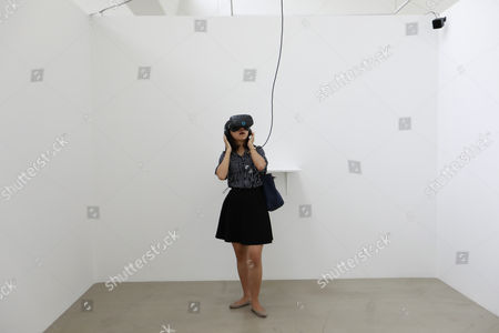 Stock Image of A visitor looks at German artist Christian Lemmerz's virtual reality (VR) artwork through a VR set during a press preview of the exhibition 'Virtual Reality Art' at Faurschou Foundation in the 798 Art district in Beijing, China, 26 August 2017. The exhibition running from 26 August  2017 to 03 February 2018 will showcase VR art works by five participating artists which include Christian Lemmerz, Erik Parker, Paul McCarthy, Tony Oursler and Yu Hong in five consecutive sub-exhibitions.