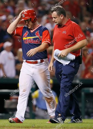 St. Louis Cardinals' Jedd Gyorko, left, leaves the game with the help of Cardinals trainer Chris Conroy after being injured rounding third during the eighth inning of a baseball game against the Tampa Bay Rays, in St. Louis