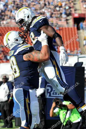 Los Angeles, CA.Los Angeles Chargers running back Melvin Gordon #28 is lifted by teammate Los Angeles Chargers center Matt Slauson #68 after he runs in for the touchdown in action in the first half during the NFL football game against the Los Angeles Rams at the Los Angeles Memorial Coliseum in Los Angeles, California..Mandatory Photo Credit: Louis Lopez/CSM