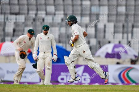 Bangladesh's Nasir Hossain, runs from the field as play is stopped due to rain on the first day of the of the first test cricket match between Bangladesh and Australia in Dhaka, Bangladesh