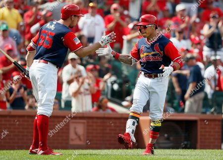 St. Louis Cardinals' Kolten Wong, right, is congratulated by teammate Stephen Piscotty after hitting a solo home run during the seventh inning of a baseball game against the Tampa Bay Rays, in St. Louis