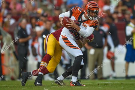 Washington Redskins linebacker Pete Robertson (58) tackles Cincinnati Bengals punter Kevin Huber (10) in the backfield after penetrating the line during the pre-season matchup between the Cincinnati Bengals and the Washington Redskins at FedEx Field in Landover, MD