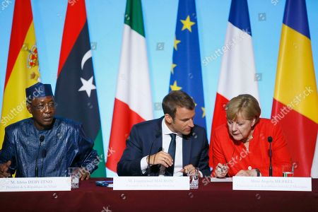 Chad's President Idriss Deby Itno, left, addresses the media during a joint press conference with German Chancellor Angela Merkel, right, and France's President Emmanuel Macron after their meeting at the Elysee Palace, in Paris, France, . The leaders of France, Germany, Italy and Spain are meeting with African counterparts to find ways to curb illegal migration across the Mediterranean to European shores