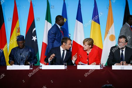 France's President Emmanuel Macron, center left, German Chancellor Angela Merkel, center right, Spain's Prime Minister Mariano Rajoy, right, and Chad's President Idriss Deby Itno, left, attend a joint press conference after their meeting at the Elysee Palace, in Paris, France, . The leaders of France, Germany, Italy and Spain are meeting with African counterparts to find ways to curb illegal migration across the Mediterranean to European shores