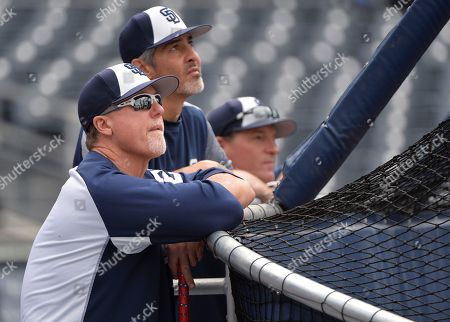 San Diego Padres bench coach Mark McGwire, left, hitting coach Alan Zinter, center, and pitching coach Darren Balsley watch batting practice before the baseball game against the San Francisco Giants, in San Diego