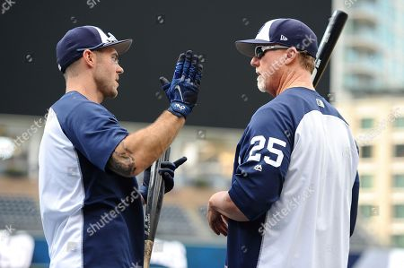 San Diego Padres bench coach Mark McGwire, right, and Matt Szczur talk during batting practice before the baseball game against the San Francisco Giants, in San Diego