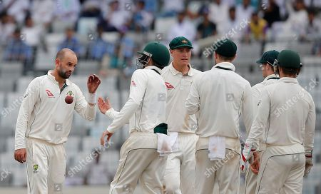 Australia's Nathan Lyon, left, and his teammates celebrate the dismissal of Bangladesh's Nasir Hossain during the third day of their first test cricket match against Dhaka, Bangladesh