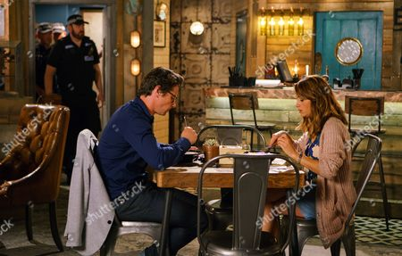 Stock Image of Ep 9244 Friday 8th September 2017 - 1st Ep Will, as played by Leon Ockenden, invites Maria Connor, as played by Samia Smith, to meet him for lunch at the bistro. Oblivious to his plotting, Maria readily agrees. Will then calls in the bistro and when nobody's looking, plants drugs in the first aid box. Taking out his phone, he then tips off the police. As Maria joins him for lunch, Rana Nazir, as played by Bhavna Limbachia, takes Zeedan Nazir, as played by Qasim Ahktar, by surprise in the bistro kitchen, causing him to cut himself. Michelle Connor, as played by Kym Marsh, pulls out the first aid box but when she opens it, she's shocked to find a bag of drugs. As Michelle, Zeedan, Kate, Daniel and Rana stare at the drugs in horror, the police arrive with sniffer dogs. Will watches in excitement.