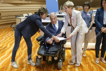 The alternative report of Inclusion Handicap passes from Verena Kuonen, right, membre of Inclusion Handicap, to Christian Lohr, right, member of the Swiss National Council, and former Swiss Federal President Micheline Calmy-Rey, left, before its delivered to chairperson, prior the 18th session of CRPD, at the European headquarters of the United Nations in Geneva, Switzerland, 29 August 2017.