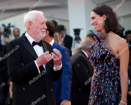 """David Stratton, Rebecca Hall Jury members David Stratton, left, and Rebecca Hall talk as they arrive on the red carpet of the premiere of the film """"Downsizing"""" which opens the 74th edition of the Venice Film Festival in Venice"""
