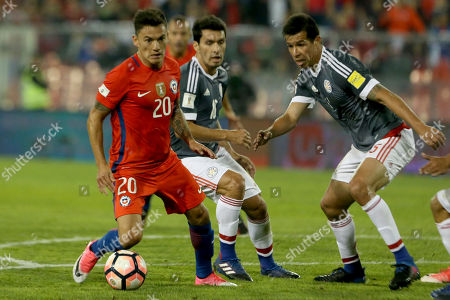 Chile's Charles Aranguiz, left, controls the ball pressures by Paraguay's Cristian Riveros, center, and Victor Caceres during a 2018 World Cup qualifying soccer match in Santiago, Chile