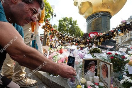 Stock Picture of A man take a mobile phone photo of the tributes to the late Princess Diana above the Post de l'Alma tunnel in Paris.  Princess Diana died with Dodi Al-Fayed in a car crash on 31st August 1997.