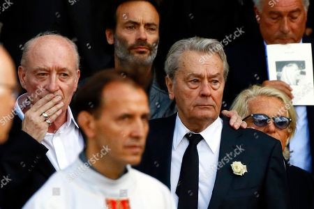 """French actor Alain Delon, center right, his son Anthony Delon, background, leaves the funeral ceremony for French actress Mireille Darc, with Darc's husband Pascal Desprez, left, and Veronique de Villele, right, at Saint Sulpice church in Paris, . Darc, with a distinctive blond bob, was long seen as a sex symbol and was a fixture on French screens in the 1960s and 1970s. She performed in some 50 films, including Jean-Luc Godard's """"Weekend"""" and Yves Robert's """"The Tall Blond with One Black Shoe"""