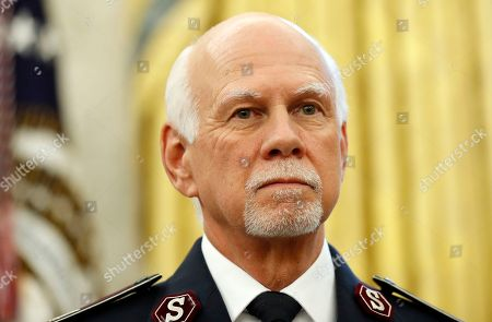 Stock Picture of Commissioner David Hudson, National Commander, of the Salvation Army USA stands as President Donald Trump speaks about Harvey in the Oval Office of the White House, in Washington