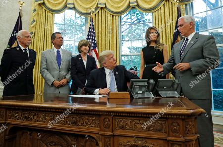 Donald Trump, David Hudson, Kevin Ezell, Gail McGovern, Mike Pence, Melania Trump President Donald Trump looks at Vice President Mike Pence as he speaks about Harvey in the Oval Office of the White House with Commissioner David Hudson, National Commander, Salvation Army USA, left, Kevin Ezell, President of Southern Baptist Disaster Relief, American Red Cross CEO Gail McGovern, and first lady Melania Trump, in Washington