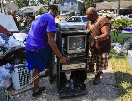 Reginald Brown (R) moves an entertainment center from his flooded home as the clean up process begins in the aftermath of Hurricane Harvey in Houston, Texas, USA, 01 September 2017. Hurricane Harvey made landfall on the south coast of Texas as a major hurricane category 4. The last time a major hurricane of this size hit the United States was in 2005.