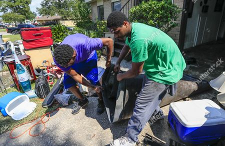 Two men help remove flood debris from the home of Reginald Brown as the clean up process begins for victims in the aftermath of Hurricane Harvey in Houston, Texas, USA, 01 September 2017. Hurricane Harvey made landfall on the south coast of Texas as a major hurricane category 4. The last time a major hurricane of this size hit the United States was in 2005.