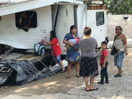 Josefina Lopez holds her child while talking to other residents in front of a damaged trailer home on Hickory Lane in Crosby, Texas after Hurricane Harvey on