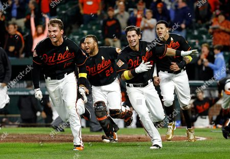 Trey Mancini, Welington Castillo, Joey Rickcard, Manny Machado Baltimore Orioles' Trey Mancini, Welington Castillo, Joey Rickcard and Manny Machado, from left, celebrate after Machado scored on Jonathan Schoop's double in the 13th inning of a baseball game against the Toronto Blue Jays in Baltimore, . Baltimore won 1-0