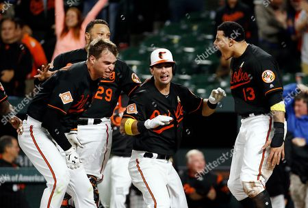 Manny Machado, Trey Mancini, Welington Castillo, Joey Rickcard Baltimore Orioles' Manny Machado, right, celebrates with teammates Trey Mancini, from left, Welington Castillo and Joey Rickcard after scoring on Jonathan Schoop's double in the 13th inning of a baseball game against the Toronto Blue Jays in Baltimore, . Baltimore won 1-0