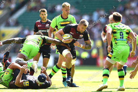 Stock Image of Dominic Day of Saracens takes on the Northampton Saints defence
