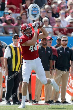 North Carolina State's Cole Cook (48) makes a catch along the sideline against South Carolina during the first half of an NCAA football game in Charlotte, N.C., . South Carolina won 35-28
