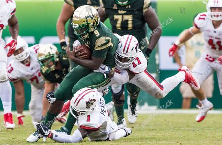 Stony Brook Seawolves defensive back Chris Cooper (17) and Stony Brook Seawolves defensive back Darin Peart (1) tackle South Florida Bulls quarterback Quinton Flowers (9) in the 2nd half during the game between the Stony Brook Seawolves and the South Florida Bulls at Raymond James Stadium in Tampa, Florida