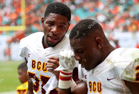 Stock Picture of Bethune Cookman Wildcats defensive back Arthur Williams (25) talks to teammate Bethune Cookman Wildcats safety Diquan Richardson (22) in the players area during the college football game between the Bethune-Cookman Wildcats and the Miami Hurricanes at the Hard Rock Stadium in Miami Gardens, Florida. The Hurricanes won 41-13