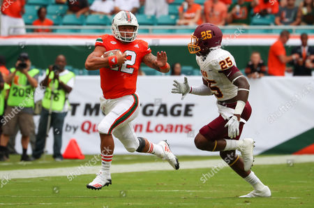 Miami Hurricanes quarterback Malik Rosier (12) runs the ball challenged by Bethune Cookman Wildcats defensive back Arthur Williams (25) during the college football game between the Bethune-Cookman Wildcats and the Miami Hurricanes at the Hard Rock Stadium in Miami Gardens, Florida. The Hurricanes won 41-13