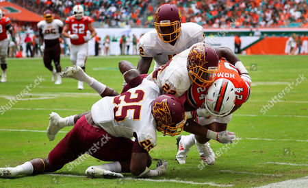 Bethune Cookman Wildcats safety Diquan Richardson (22) and Bethune Cookman Wildcats defensive back Arthur Williams (25) take down Miami Hurricanes running back Travis Homer (24) during the college football game between the Bethune-Cookman Wildcats and the Miami Hurricanes at the Hard Rock Stadium in Miami Gardens, Florida. The Hurricanes won 41-13