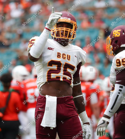Stock Image of Bethune Cookman Wildcats defensive back Arthur Williams (25) comments with teammates on a re-play on the stadium screen during the college football game between the Bethune-Cookman Wildcats and the Miami Hurricanes at the Hard Rock Stadium in Miami Gardens, Florida. The Hurricanes won 41-13