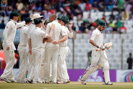 Bangladesh's Nasir Hossain, right, walks back to the pavilion after his dismissal by Australia's Ashton Agar during the second day of their second test cricket match in Chittagong, Bangladesh