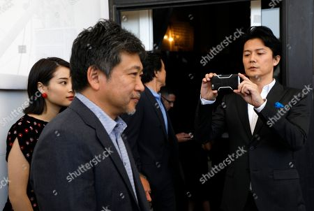 Stock Image of Actor Fukuyama Masaharu, right, films with his phone as director Kore-eda Hirokazu walks in front of him as he arrives for the photo call of the film 'Sandome No Satsujin' (The Third Murder), at the 74th edition of the Venice Film Festival, in Venice, Italy