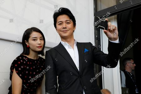 Stock Photo of Actor Fukuyama Masaharu, right, takes a selfie with actress Hirose Suzu during the photo call of the film 'Sandome No Satsujin' (The Third Murder), at the 74th edition of the Venice Film Festival, in Venice, Italy