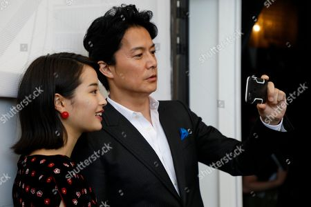 Actor Fukuyama Masaharu, right, takes a selfie with actress Hirose Suzu during the photo call of the film 'Sandome No Satsujin' (The Third Murder), at the 74th edition of the Venice Film Festival, in Venice, Italy