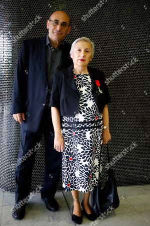 """Dr. Leyla Yunus, of the Institute for Peace and Democracy of Azerbaijan, right, with her medal of Chevalier of the French Legion of Honor poses with her husband Arif Yunus prior to the trial of French journalists Elise Lucet and Laurent Richard at the court in Nanterre, outside Paris, Tuesday, Sept.5, 2017. French journalists Lucet and Laurent Richard are on trial accused by Azerbaijan's government of defamation for calling the country a """"dictatorship."""" following a 2015 investigative report"""