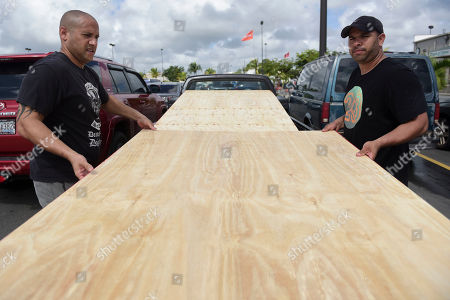 Luis Enrique Garcia, left, and Jose Rivera, load wood panels to be used for boarding up windows in preparation for Hurricane Irma, in Carolina, Puerto Rico, . Irma grew into a dangerous Category 5 storm, the most powerful seen in the Atlantic in over a decade, and roared toward islands in the northeast Caribbean Tuesday