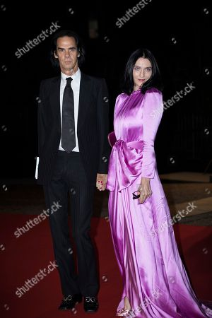 Nick Cave and Susie Bick pose for photographers upon arrival at the GQ's Men of The Year awards, in London