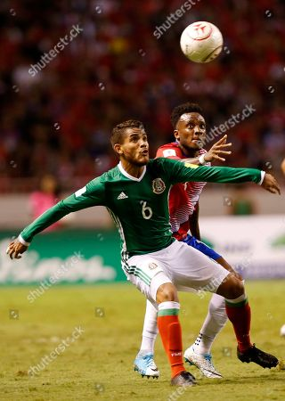 Mexico's Jonathan Dos Santos, left, fights for the ball with Costa Rica's Rodney Wallace during a 2018 Russia World Cup qualifying soccer match at the National Stadium in San Jose, Costa Rica