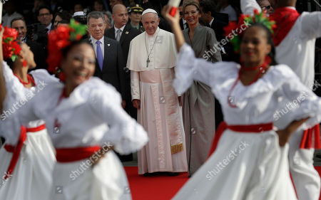 Pope Francis watches dancers perform, alongside Colombia's First Lady Maria Clemencia Rodriguez Munera, right, and President Juan Manuel Santos, left, during the pontiff's welcoming ceremony at El Dorado airport in Bogota, Colombia,. Pope Francis has arrived in Colombia for a five-day visit