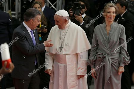 Pope Francis speaks with Colombia's President Juan Manuel Santos as First Lady Maria Clemencia Rodriguez Munera stands by at El Dorado airport after the pontiff's arrival in Bogota, Colombia,. Pope Francis has arrived in Colombia for a five-day visit