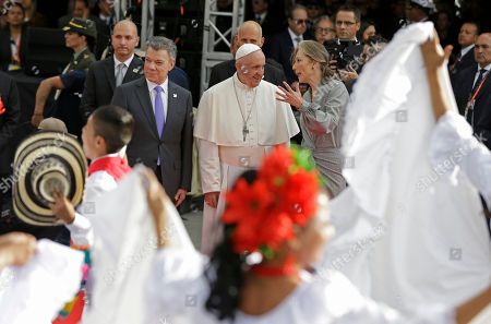 Pope Francis listens to Colombia's First Lady Maria Clemencia Rodriguez Munera as President Juan Manuel Santos stands by, watching dancers perform upon the pontiff's arrival to El Dorado airport in Bogota, Colombia,. Pope Francis has arrived to Colombia for a five-day visit