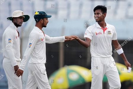 Bangladesh's Mustafizur Rahman, right, celebrates with his teammate Nasir Hossain, center, after the dismissal of Australia's Nathan Lyon during the fourth day of the second test cricket match in Chittagong, Bangladesh